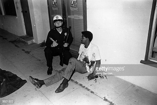 A bloodsplattered man sitting beside an armed policeman during the Watts Riots Los Angeles California 11th15th August 1965