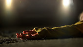 Bloody female victim of deadly car accident lying on road, close-up view at body