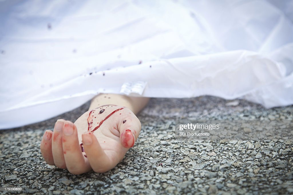 Bloody hand at an accident scene pavement : Stock Photo