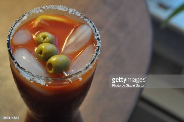 bloody mary drink with a salt-rimmed glass and olives - bloody mary stock photos and pictures