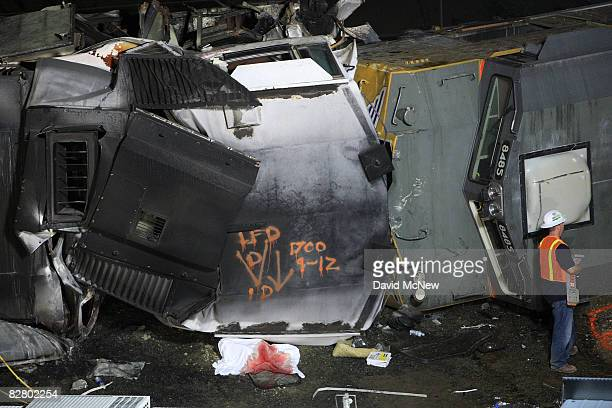 A bloody sheet covers a body under the toppled engine of a Metrolink commuter train that collided headon with the engine of a freight train on the...