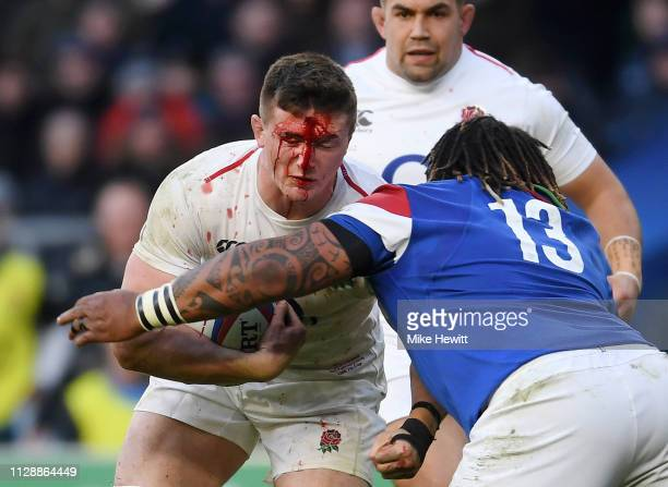 A bloody Tom Curry of England is tackled by Mathieu Bastareaud of France during the Guinness Six Nations match between England and France at...