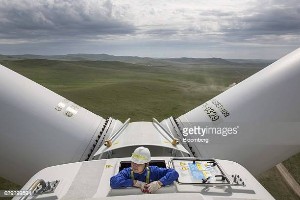 Bloomberg Best of the Year 2016: An engineer climbs out of the nacelle of a General Electric Co. Wind turbine at the Salkhit Wind Farm operated by...