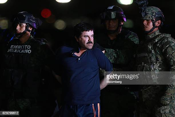 Joaquin Guzman the world's most wanteddrug trafficker center is escorted by Mexican security forces at a Navy hangar in Mexico City Mexico on Friday...
