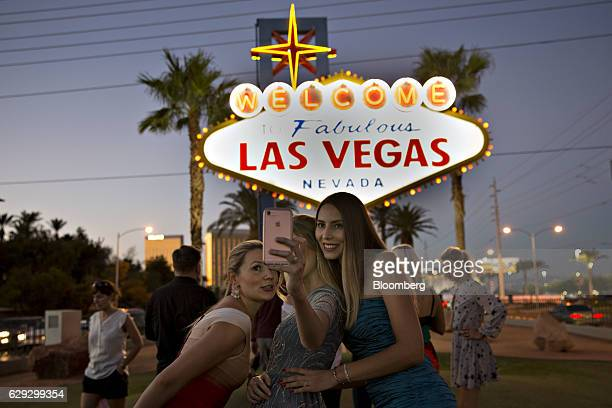 Visitors pose for a selfie photograph in front of the 'Welcome To Fabulous Las Vegas' sign at dusk ahead of the third US presidential debate in Las...
