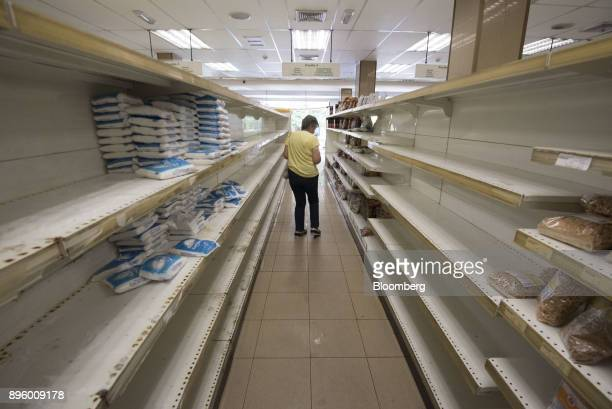 A customer moves along empty shelves as she shops for groceries at a supermarket in Caracas Venezuela on Tuesday July 25 2017 Photographer Carlos...