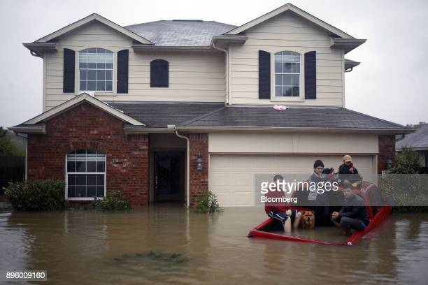 Residents with a dog sit in the back of a truck while waiting to be rescued from rising floodwaters due to Hurricane Harvey in Spring Texas US on...