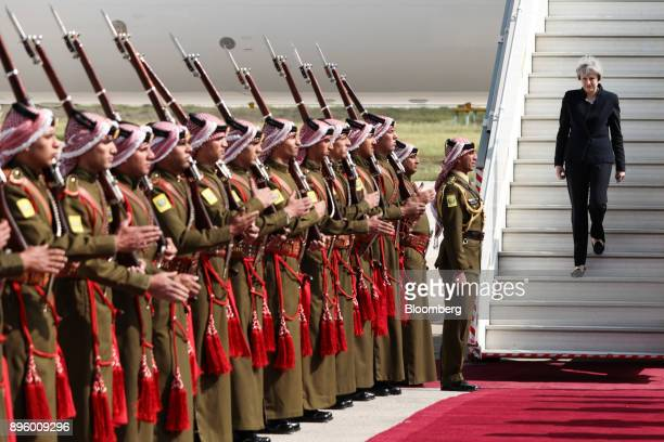 Theresa May UK prime minister walks down the aircraft steps as she prepares to inspect a military honor guard on her arrival in Amman Jordan on...