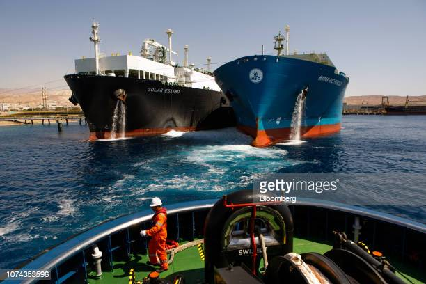 A crew member aboard the emergency standby ASD tug boat 'Tareq 3' watches as the 'Golar Eskimo' Floating Storage and Regasification Unit center right...
