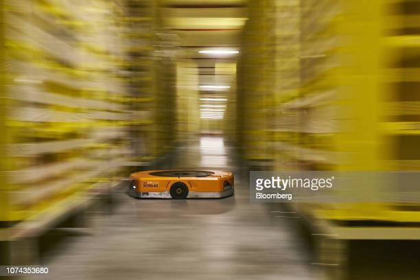 An automated transport robot moves between shelving units containing goods at Amazoncom Inc's new fulfillment center in Kolbaskowo Poland on Friday...