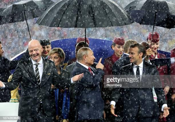 Gianni Infantino president of FIFA left Vladimir Putin Russia's president and Emmanuel Macron France's president react as rain falls during the award...