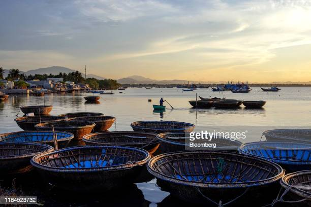 A fisherman makes his way past basket boats moored in Tan Quang harbor in Quang Nam province Vietnam on Wednesday June 26 2019 Photographer Maika...