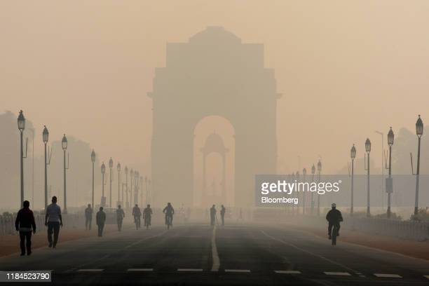 Pedestrians walk along Rajpath boulevard as India Gate monument stands shrouded in smog in New Delhi India on Tuesday Nov 5 2019 Photographer Ruhani...