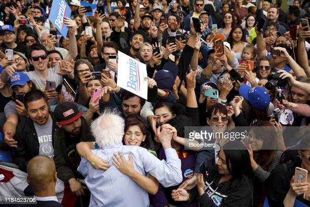 Senator Bernie Sanders an Independent from Vermont and 2020 presidential candidate bottom center is hugged by an attendee during a campaign rally in...