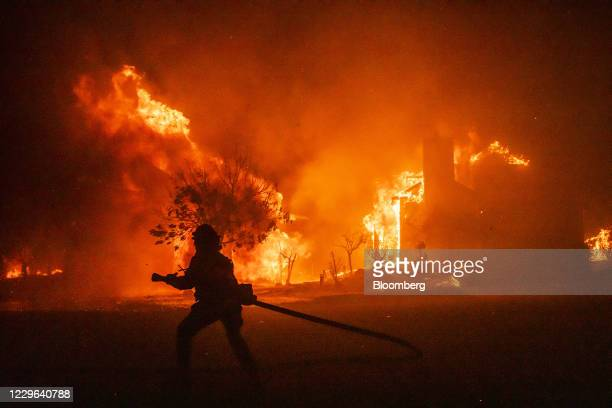 Bloomberg Best of the Year 2020: A firefighter carries a hose as buildings burn in the Skyhawk Park neighborhood of East Santa Rosa during wildfires...
