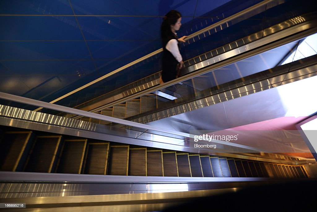 Bloomberg Photo Service 'Best of the Week': A woman rides on an escalator in the Roppongi Hills Mori Tower, operated by Mori Building Co., in Tokyo, Japan, on Wednesday, April 17, 2013. While financial firms have cut staff in Japan, technology companies have boosted hiring, and as bankers vacated offices at Roppongi Hills, companies including Google Inc. and Lenovo Group Ltd. moved in. As early as this month, Apple Inc. will also make the complex its home in Japan, two people familiar with the plan said in January. Photographer: Tomohiro Ohsumi/Bloomberg via Getty Images