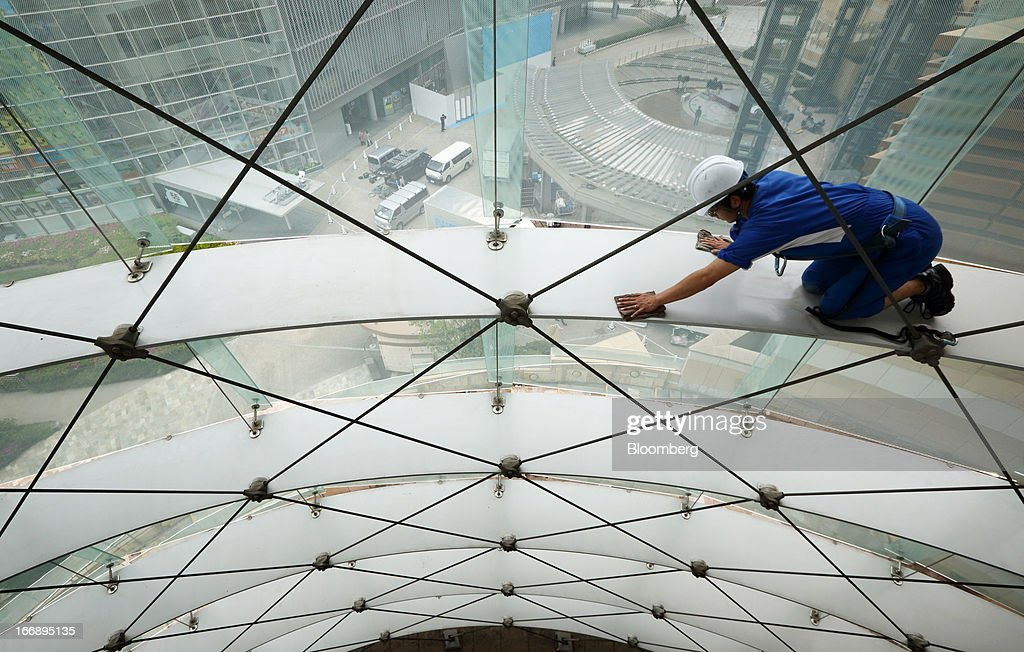Bloomberg Photo Service 'Best of the Week': A worker cleans the windows inside the Roppongi Hills Mori Tower, operated by Mori Building Co., in Tokyo, Japan, on Wednesday, April 17, 2013. While financial firms have cut staff in Japan, technology companies have boosted hiring, and as bankers vacated offices at Roppongi Hills, companies including Google Inc. and Lenovo Group Ltd. moved in. As early as this month, Apple Inc. will also make the complex its home in Japan, two people familiar with the plan said in January. Photographer: Tomohiro Ohsumi/Bloomberg via Getty Images
