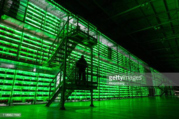 Tech Unchecked An armed guard patrols in front of illuminated mining rigs mounted inside racks at the BitRiver Rus LLC cryptocurrency mining farm in...
