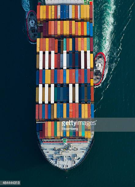 Bloomberg's Best Photos 2013 Tugboats help guide a Mediterranean Shipping Co ship loaded with freight containers in this aerial photograph...