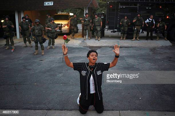 Bloomberg's Best Photos 2014: A demonstrator holding a red rose kneels in front of armed police officers and raises their hands above her head during...