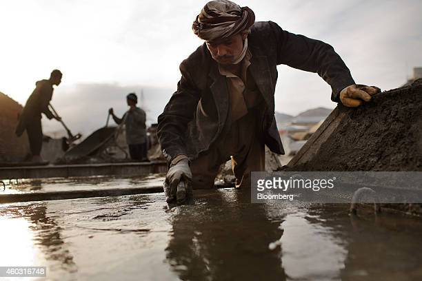 Bloomberg's Best Photos 2014 A laborer smoothes out concrete while building blast walls at a facility north of Kabul Afghanistan on Monday April 14...