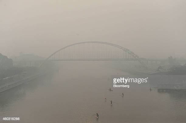 Bloomberg's Best Photos 2014 A new bridge under construction over the Siak river stands shrouded in haze as kayakers paddle past in Pekanbaru Riau...