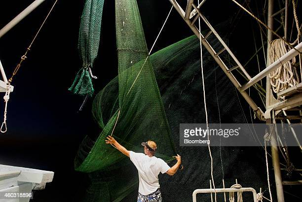 Bloomberg's Best Photos 2014 A shrimper ties up the nets after a day's catch on a shrimping boat off the coast of Grand Isle Louisiana US on...