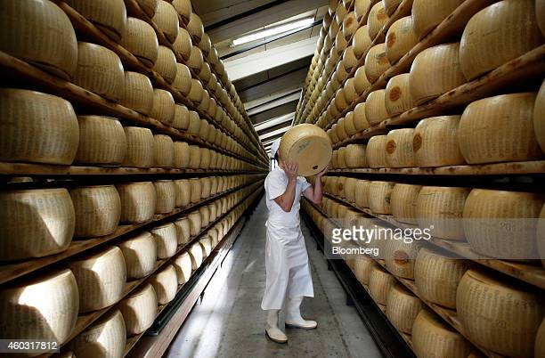 Bloomberg's Best Photos 2014 A worker selects a whole ParmigianoReggiano cheese from a storage rack ahead of inspection at Coduro cheesemakers in...