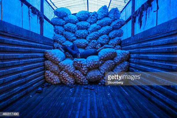 Bloomberg's Best Photos 2014 A worker takes a nap while lying on sacks of onions on a truck at the Vashi Agricultural Produce Market Committee...