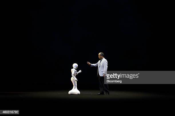 Bloomberg's Best Photos 2014 Billionaire Masayoshi Son chairman and chief executive officer of SoftBank Corp right gestures towards a humanlike robot...