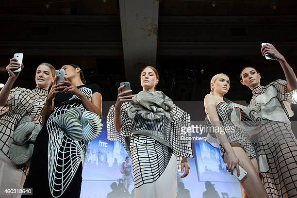 Bloomberg's Best Photos 2014 Models pose for photographs with HTC Corp's HTC Desire Eye smartphones during an unveiling event in New York US on...