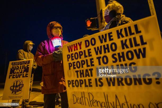 Bloomington anti-death-penalty activist Glenda Breeden holds a lamp while protesting against the execution of Lisa Montgomery, and two others, which...