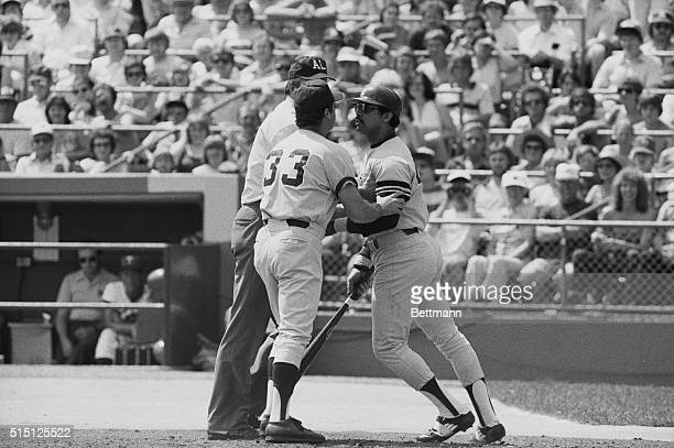 New York Yankees' Reggie Jackson holds his bat and attempts to push his way past Yankees' coach Mike Ferraro to reach Minnesota Twins' pitcher Jerry...
