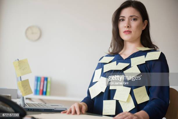 Blouse of stressed Caucasian businesswoman covered with adhesive notes