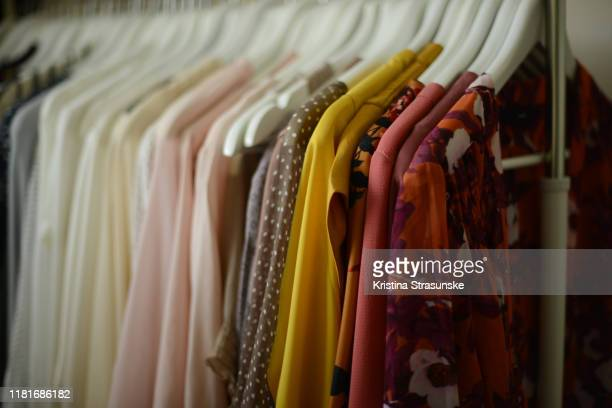 blouses arranged by color hanged on hangers in a row - kristina strasunske stock pictures, royalty-free photos & images