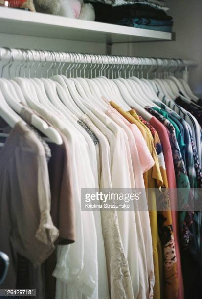 blouses in different colors hanging on a coathangers, arranged by color - kristina strasunske stock pictures, royalty-free photos & images
