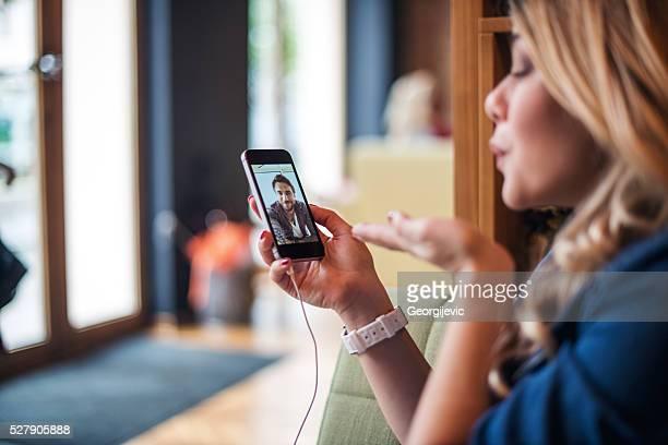 blowing a kuss - video call stock-fotos und bilder