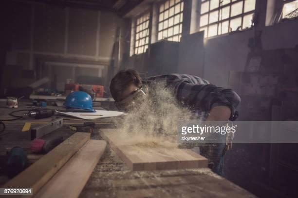 Het stof van een plank wegblazen in een winkel timmerwerk!