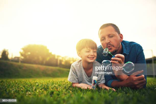 blowing bubbles in the backyard is my favourite - one parent stock pictures, royalty-free photos & images