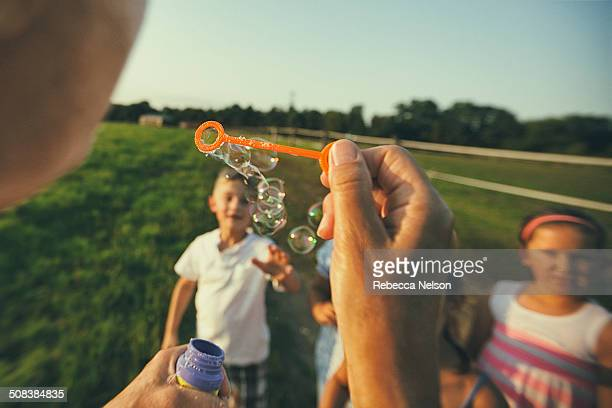 blowing bubbles to children - personal perspective stock pictures, royalty-free photos & images