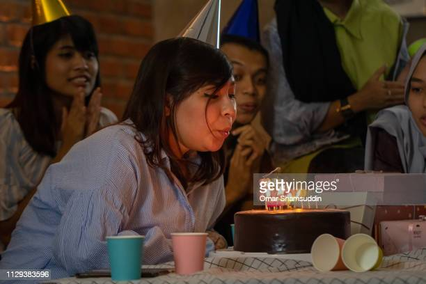 Blowing candles on birthday cake with friends