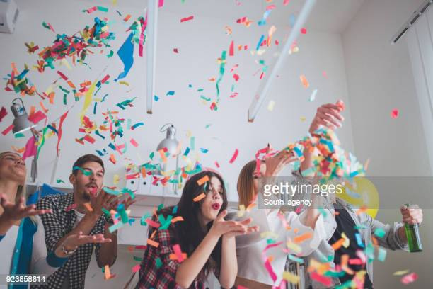 blowing confetti on party - work party stock pictures, royalty-free photos & images