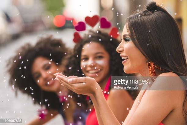 blowing confetti - carnival stock photos and pictures