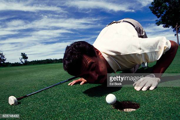 Blowing golf ball into hole