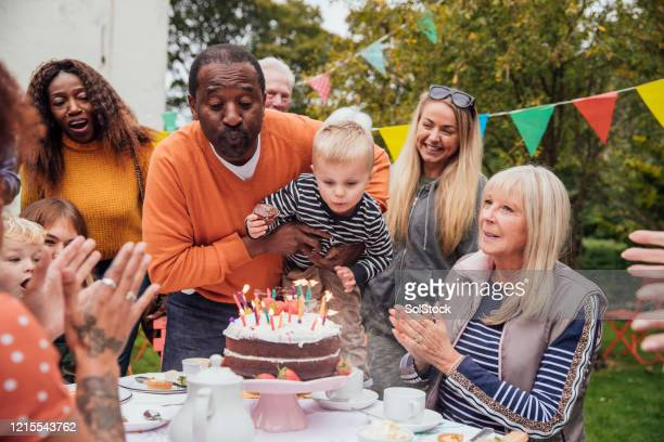 blowing out the candles - birthday cake stock pictures, royalty-free photos & images