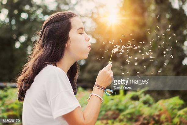 blowing up a dandelion