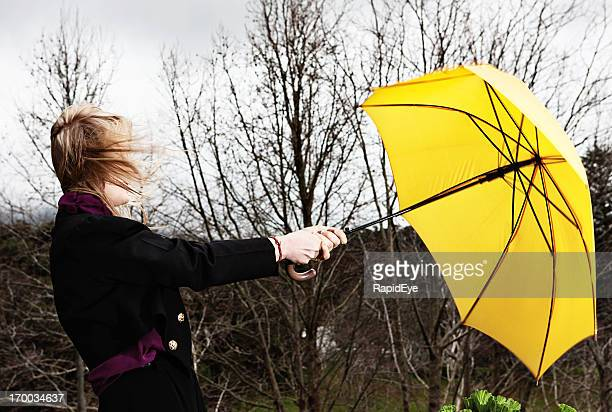 Blown away: young woman with yellow umbrella on stormy day