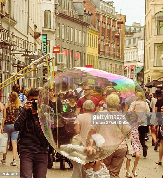 Blown Colorful Oversized Soap Bubble In Front Of Crowd