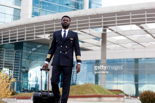 bluck airline pilot pulling his lagguge airport terminal - piloting stock pictures, royalty-free photos & images