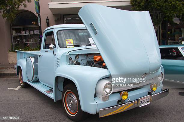 Saratoga, California, United States - July 19, 2015: Blue vintage Ford pickup with an open hood parked on a city street alongside a cafe